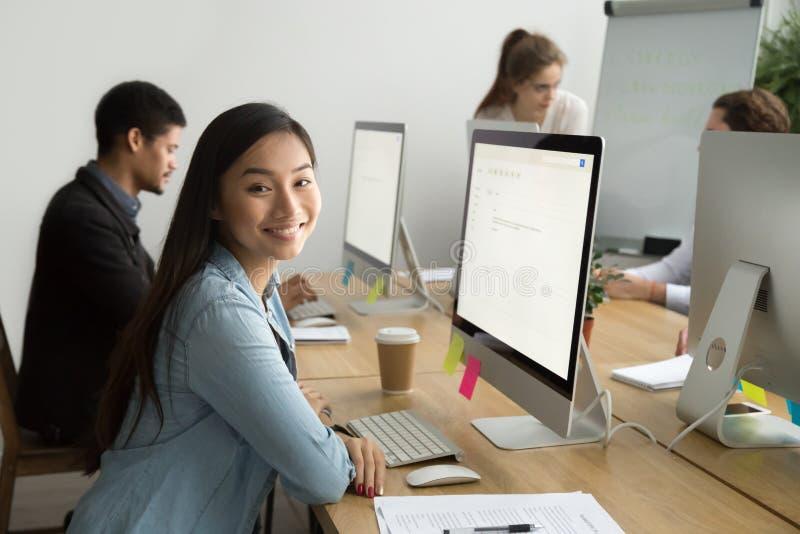 Усмехаясь азиатский работник офиса смотря камеру работая с col стоковое фото