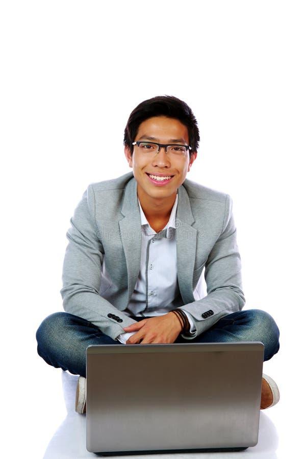 Усмехаясь азиатский человек сидя на поле стоковые изображения