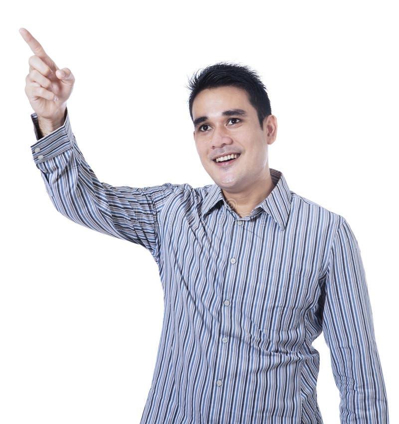 Усмехаясь азиатский человек указывая на что-то стоковые фото