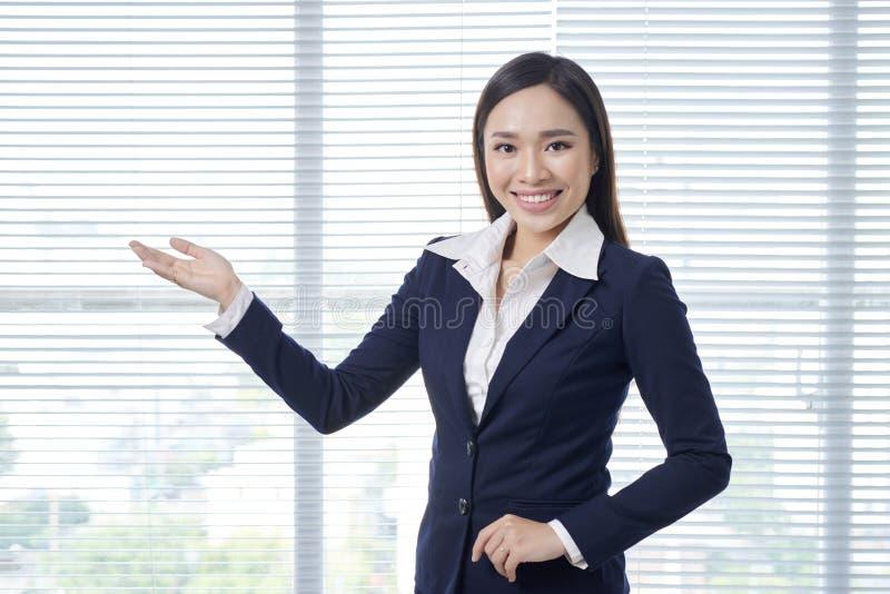 Усмехаясь азиатское положение коммерсантки в ярком офисе стоковые фотографии rf