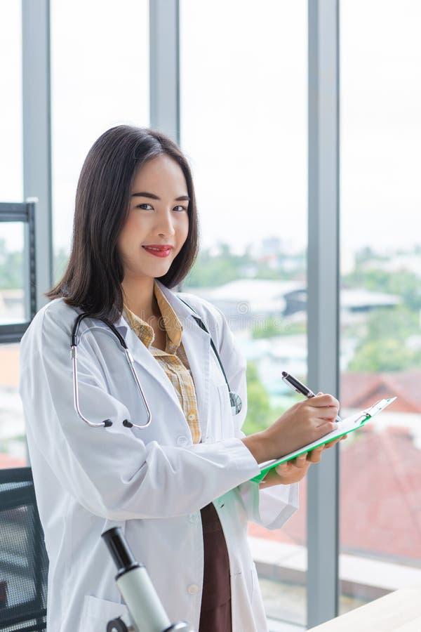 Усмехаясь азиатское сочинительство женщины доктора диетолога на бумажной зеленой доске в комнате лаборатории стоковая фотография rf