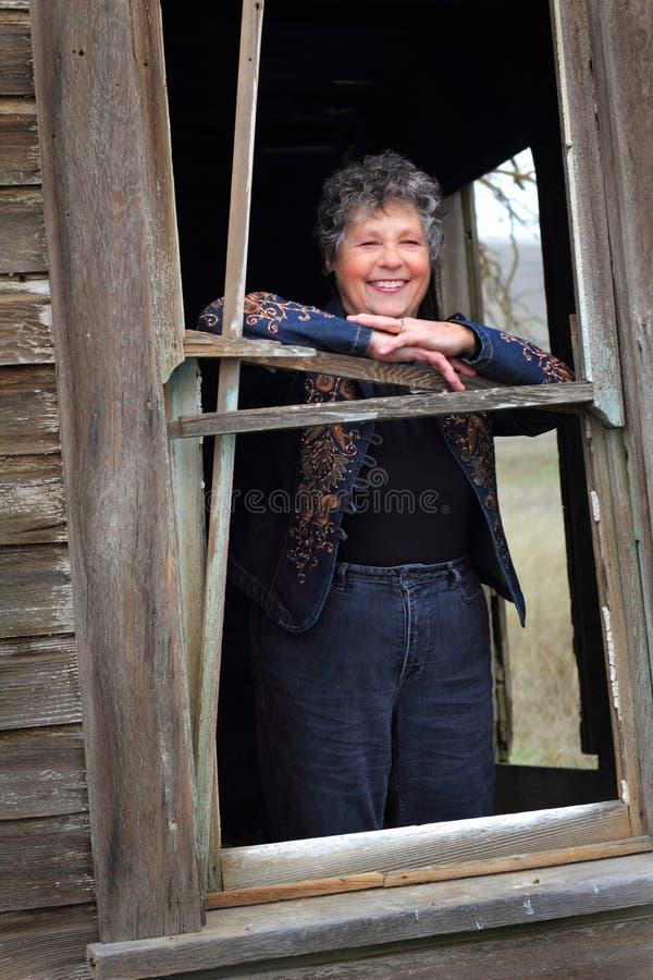 Усмехаясь дама в окне стоковое фото rf