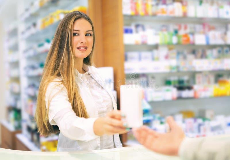 Усмехаясь аптекарь давая ей пилюльки клиента на аптеке стоковое фото