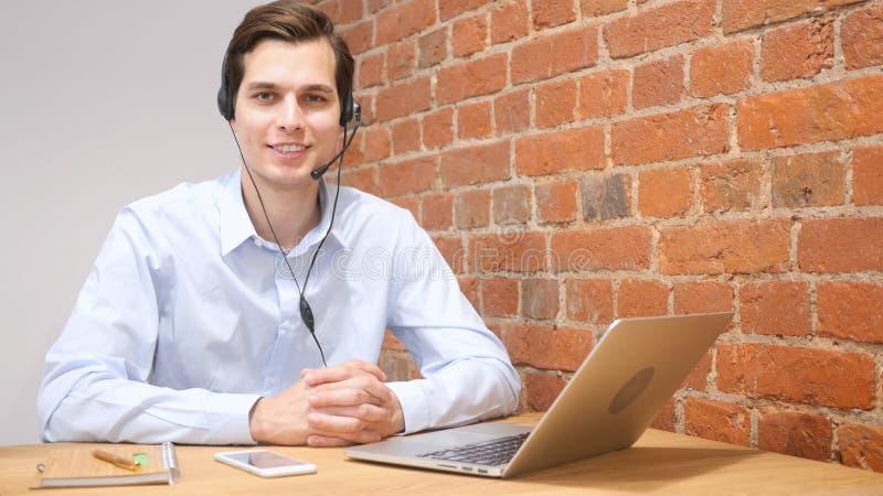 Усмехаясь ассистент используя шлемофон в центре телефонного обслуживания, онлайн обслуживании клиента стоковое фото rf