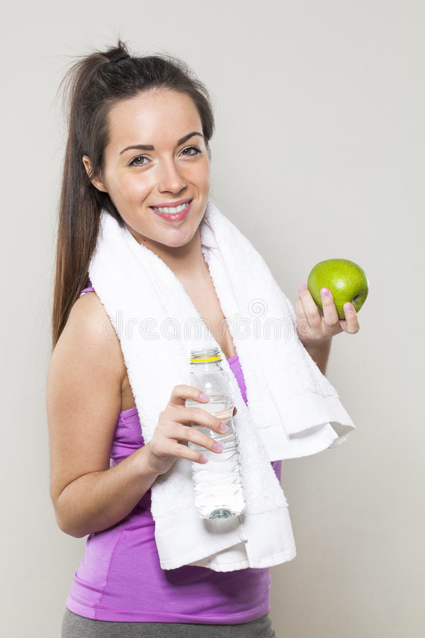 Усмехаясь атлетическая девушка 20s с символами здоровья и питания для sporty образа жизни в руках стоковые фотографии rf