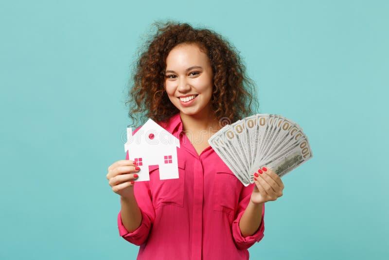 Усмехаясь африканская девушка в случайных одеждах держа бумажный дом, вентилятор денег в банкнотах доллара, денег наличных денег  стоковая фотография