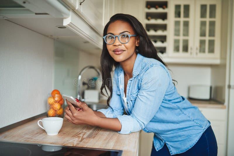 Усмехаясь африканская женщина полагаясь на ее счетчике кухни отправляя tex стоковая фотография rf
