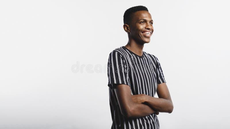 Усмехаясь африканский человек с оружиями пересек стоковые фотографии rf