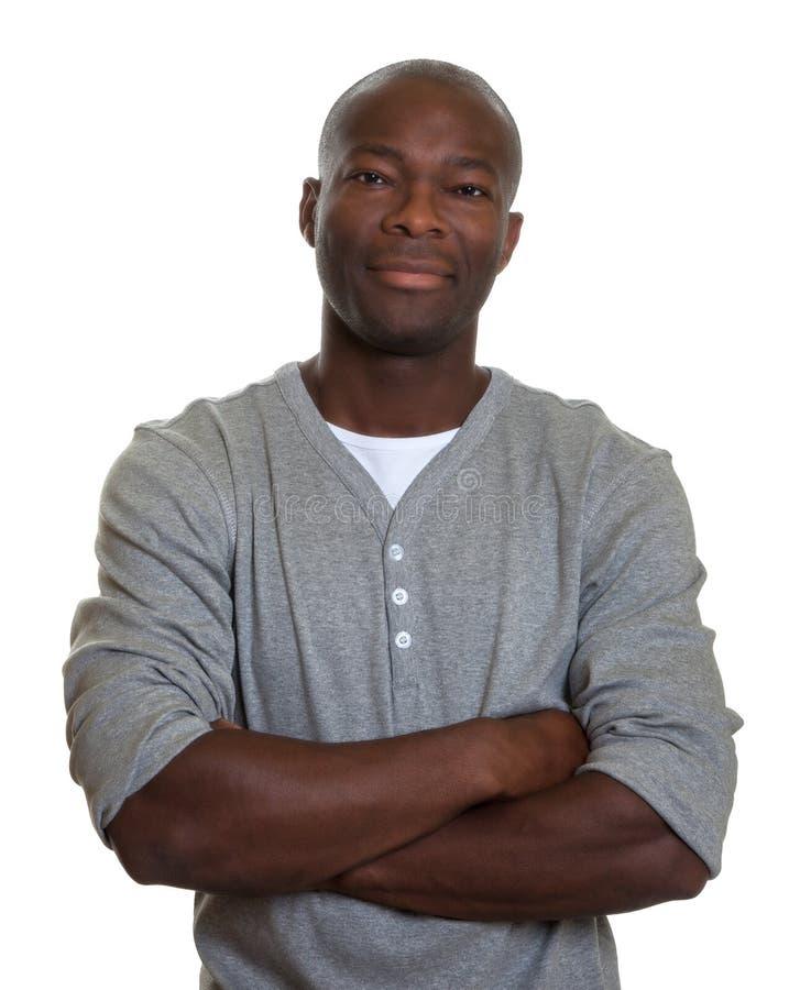Усмехаясь африканский человек в серой рубашке с пересеченными оружиями стоковые изображения rf