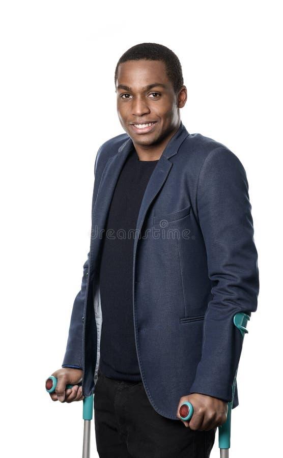 Усмехаясь африканский человек на костылях стоковая фотография