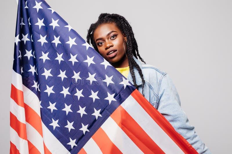 Усмехаясь афро американская женщина держа флаг США и смотря камеру изолированную над серой предпосылкой стоковое изображение rf