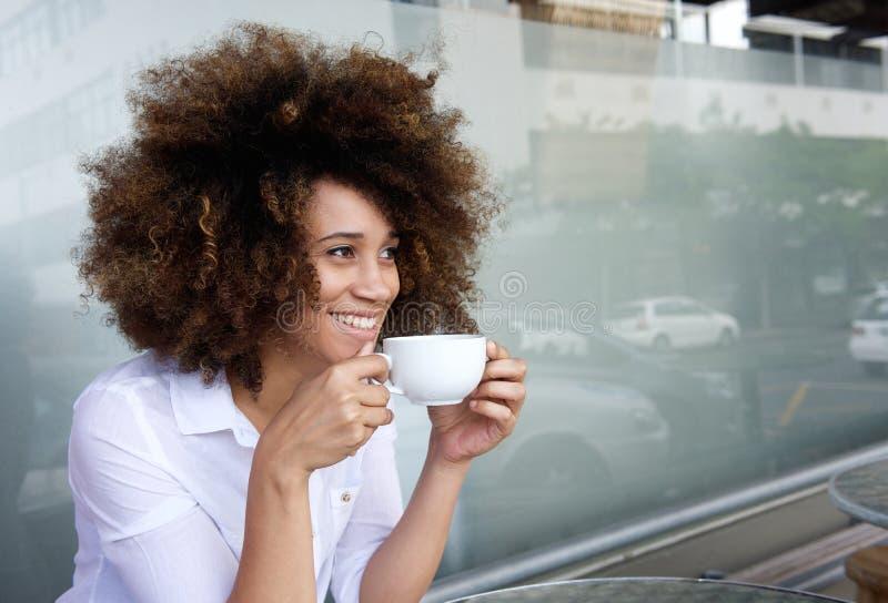 Усмехаясь Афро-американская женщина сидя с чашкой кофе стоковое изображение