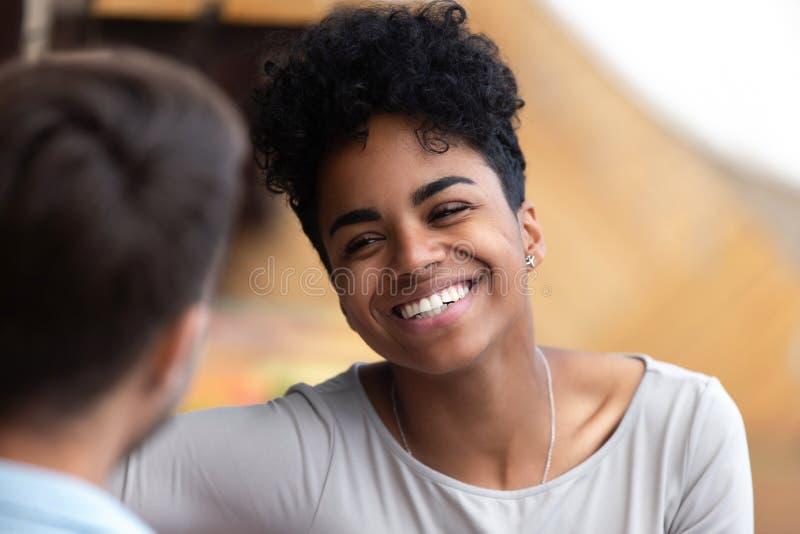 Усмехаясь Афро-американская женщина смотря конец человека вверх стоковые фото