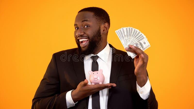 Усмехаясь афро-американский бизнесмен держа наличные деньги piggybank и доллара, депозит стоковые изображения rf