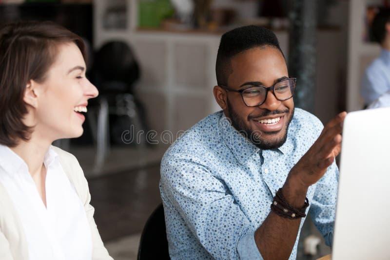 Усмехаясь Афро-американский человек разговаривая с женским коллегой стоковые изображения