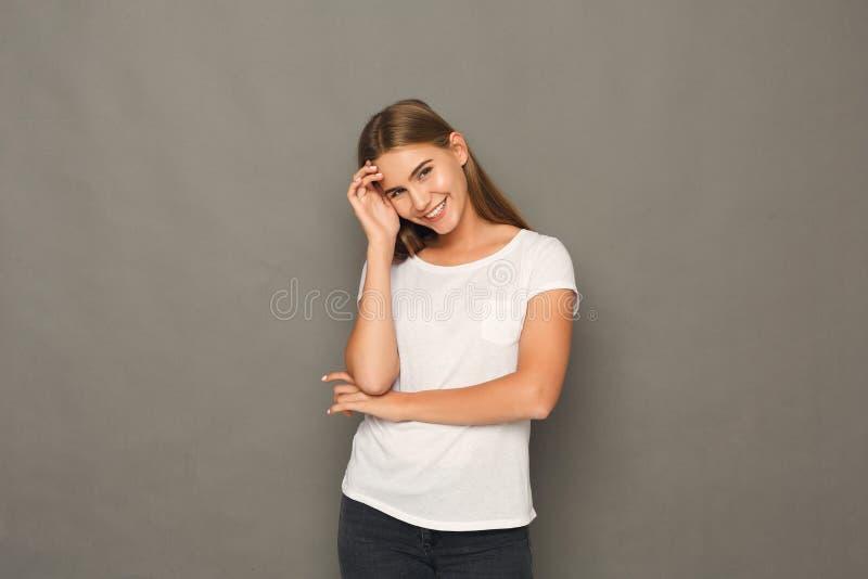 Усмехаясь белокурая девушка представляя на студии стоковая фотография