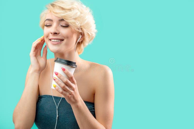 Усмехаясь белокурая девушка слушает к ее любимой музыке стоковые фотографии rf