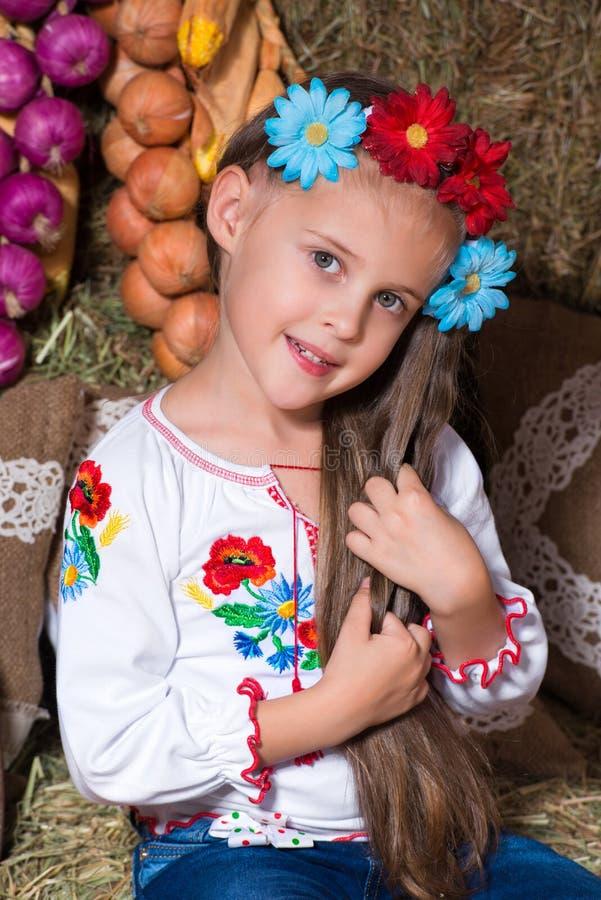 Усмехаясь белокурая девушка с длинными волосами в красочном украинском венке и в вышитый сидит на стогах сена Оформление осени, с стоковое фото rf