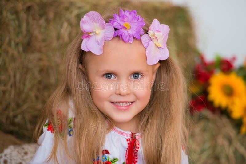 Усмехаясь белокурая девушка с длинными волосами в красочном украинском венке и в вышитый сидит на стогах сена Оформление осени, с стоковые фотографии rf