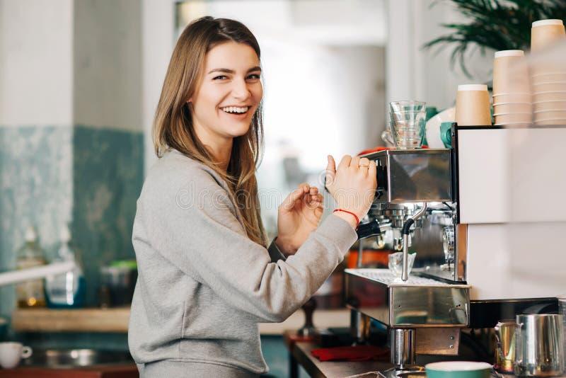 Усмехаясь белокурая женщина на машине кофе в кафе стоковое изображение