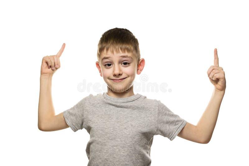 Усмехаясь белокурый мальчик в стойках и пунктах серых футболки с указательными пальцами вверх Изолят на белой предпосылке стоковое фото rf