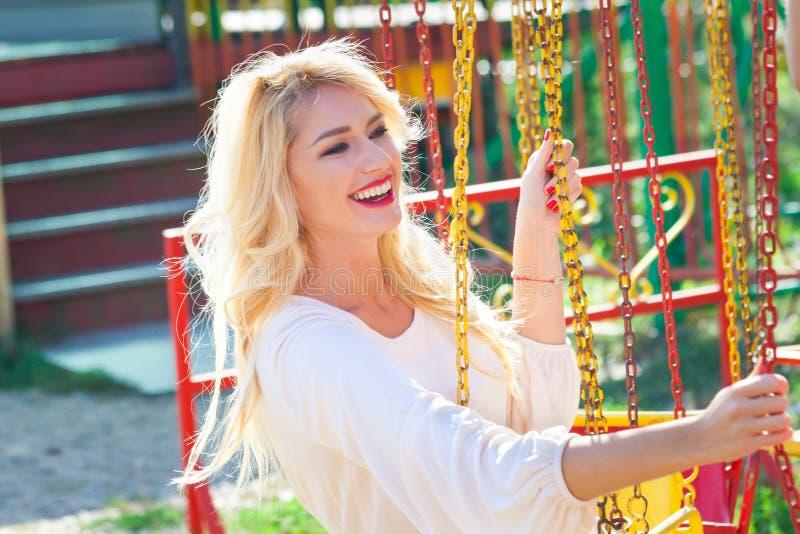 Усмехаясь белокурый молодой портрет элегантной женщины в занятности Пак на летний день летая carousel стоковое фото