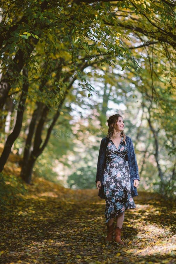 Усмехаясь беременная женщина идя в лес осени стоковое изображение rf