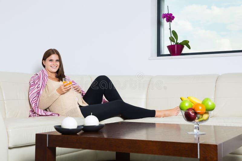 Усмехаясь беременная женщина с стеклом апельсинового сока стоковые фото