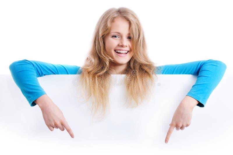 Усмехаясь белокурая девушка указывая ее пальцы вниз стоковое фото rf