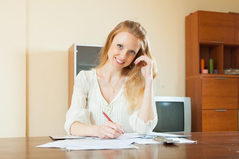 Усмехаясь белокурая женщина заполняет внутри документы стоковые фотографии rf