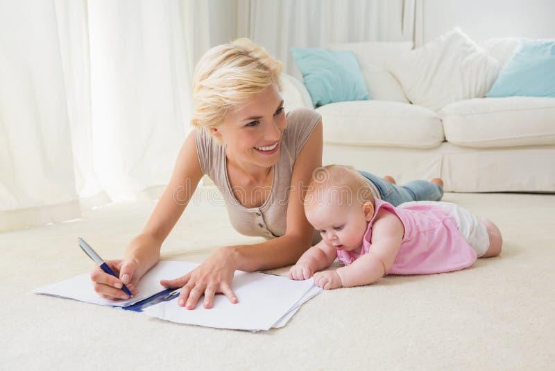Усмехаясь белокурая мать с ее сочинительством ребёнка на тетради с прописями стоковая фотография rf