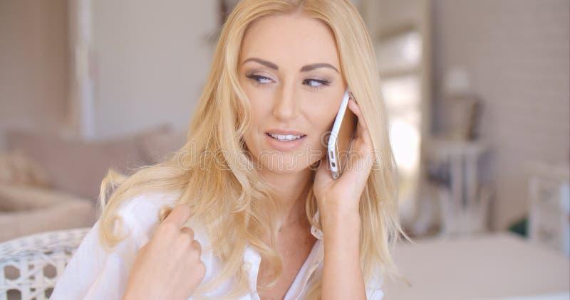 Усмехаясь белокурый женский говорить через телефон стоковая фотография