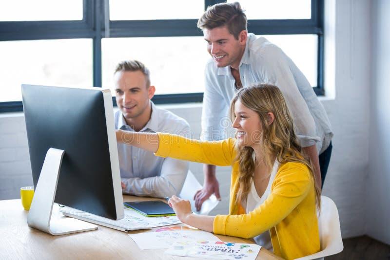 Усмехаясь бизнесмены обсуждая над компьютером стоковое фото