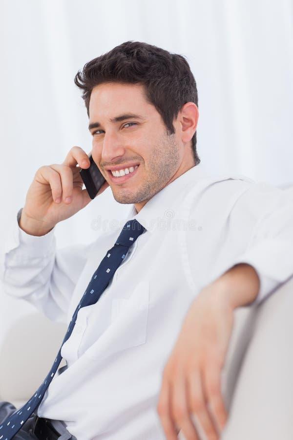 Download Усмехаясь бизнесмен вызывая с его мобильным телефоном на софе Стоковое Изображение - изображение насчитывающей усаживание, brussels: 33739351