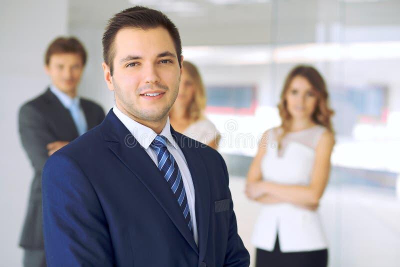 Усмехаясь бизнесмен в офисе с коллегами на заднем плане стоковое изображение