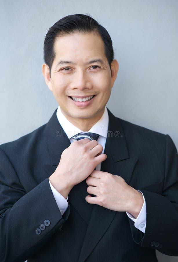 Download Усмехаясь бизнесмен держа галстук Стоковое Изображение - изображение насчитывающей черный, официально: 41653563