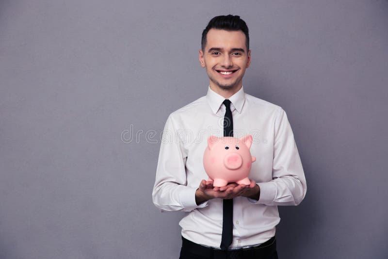Усмехаясь бизнесмен держа денежный ящик свиньи стоковые фото