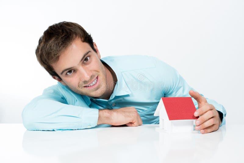 Усмехаясь бизнесмен защищая малый дом стоковое изображение