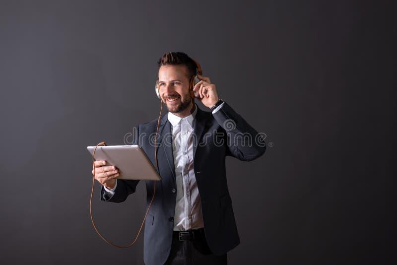 Усмехаясь бизнесмен используя планшет и слушающ к музыке стоковые фото