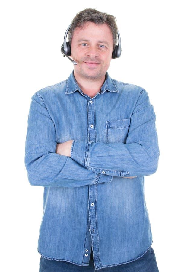 Усмехаясь бизнесмен используя шлемофон говоря с клиентом в центре телефонного обслуживания стоковое изображение