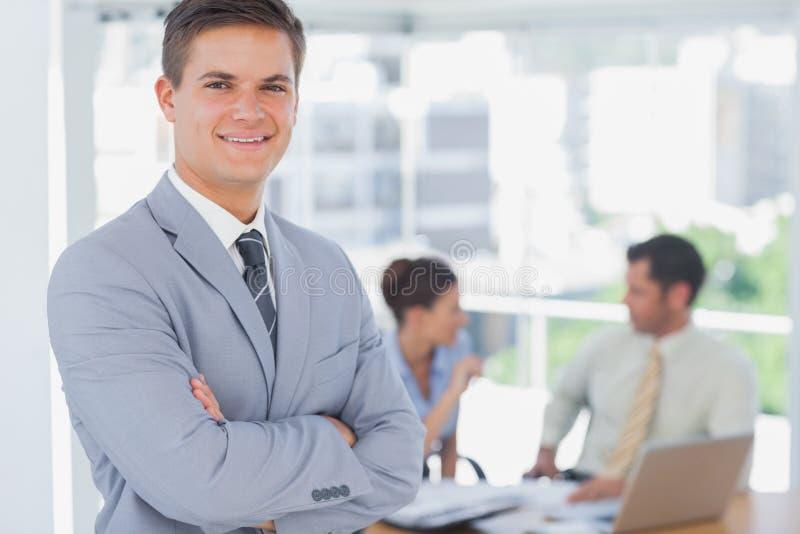 Усмехаясь бизнесмен и его коллеги в предпосылке стоковое изображение
