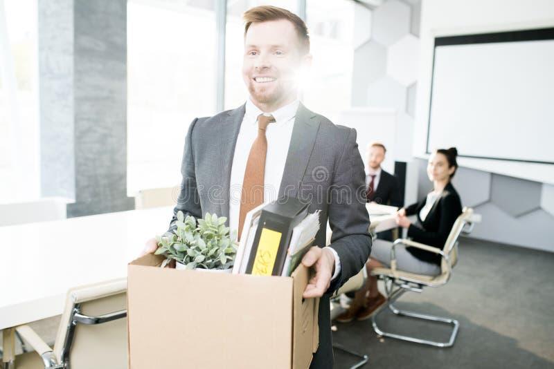 Усмехаясь бизнесмен прекращая работу стоковое фото rf