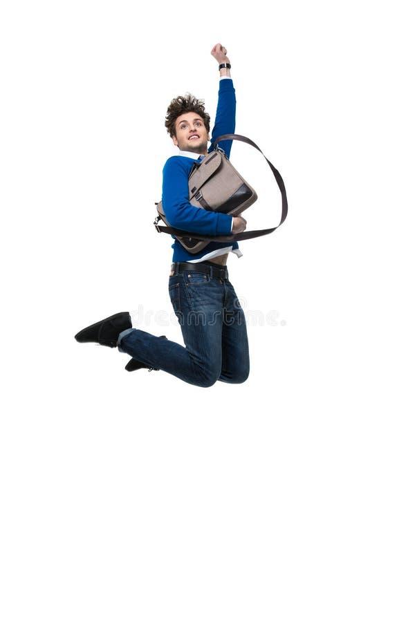Усмехаясь бизнесмен скача с сумкой стоковые фото