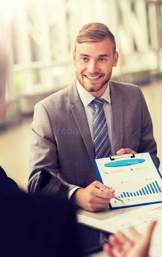 Усмехаясь бизнесмен с диаграммой на деловой встрече стоковое фото rf