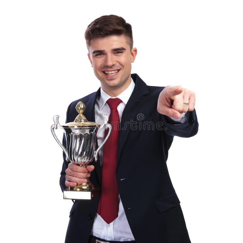 Усмехаясь бизнесмен указывает палец пока держащ награженное trop стоковое изображение