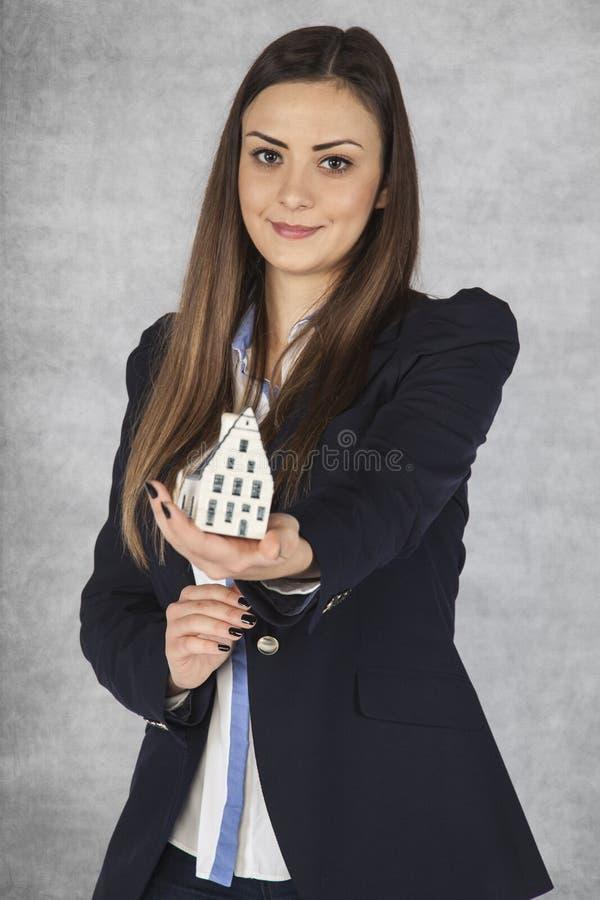 Усмехаясь бизнес-леди дает небольшой дом стоковые фотографии rf