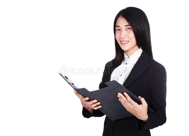 Усмехаясь бизнес-леди в костюме держа доску сзажимом для бумаги изолированный на w стоковая фотография rf