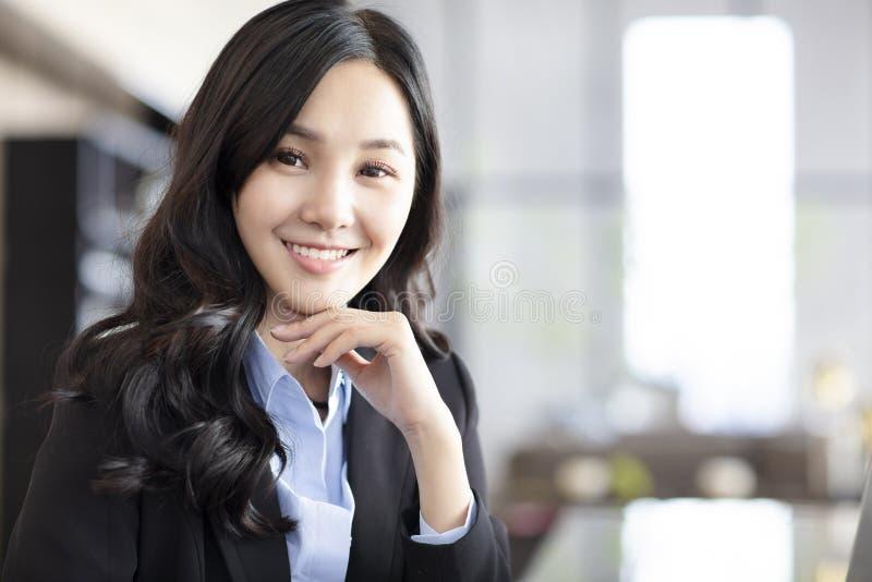Усмехаясь бизнес-леди в офисе стоковое изображение rf
