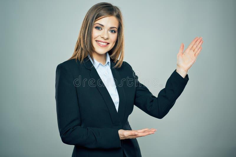 Усмехаясь бизнес-леди показывая руку скопируйте космос стоковое фото