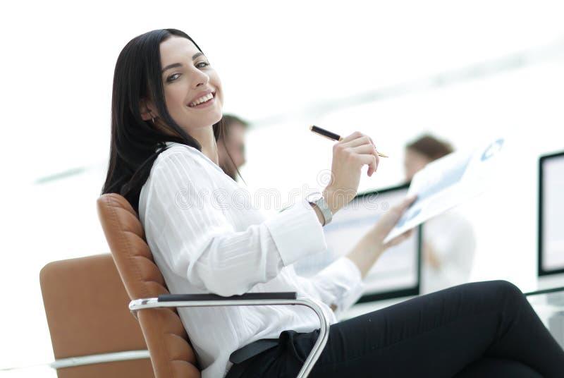 Усмехаясь бизнес-леди при финансовые документы сидя на столе работы стоковое изображение rf